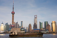 View of a barge on the Huangpu River and the Pudong financial and business district from the Bund, China