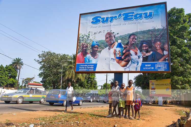 Children stand under a billboard advertising Sur'Eau on a busy street through Guinea's capital city of Conakry.  Sur'Eau is a chlorine product that makes water safe to drink and is distributed by the international social marketing organization, Population Services International (PSI).