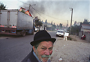 A Kalderash Roma elder on the road that runs through the Roma camp of SIntesti. The smoke filling the sky comes from the Kaldersh Roma melting scrap metal to make ingots of pure metal to sell to metal foundries. The camp is home to approximately 1000 Roma..
