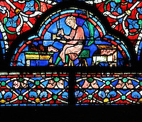 A cobbler at work in his workshop, piercing holes in a shoe for the laces, a typical style of the 13th century, part of the donor section of the shoemakers at the bottom of the Glorification of the Virgin stained glass window, in the nave of Chartres Cathedral, Eure-et-Loir, France. This window depicts the end of the Virgin's life on earth, her dormition and assumption, as told in the apocryphal text the Golden Legend of 1260. Chartres cathedral was built 1194-1250 and is a fine example of Gothic architecture. Most of its windows date from 1205-40 although a few earlier 12th century examples are also intact. It was declared a UNESCO World Heritage Site in 1979. Picture by Manuel Cohen