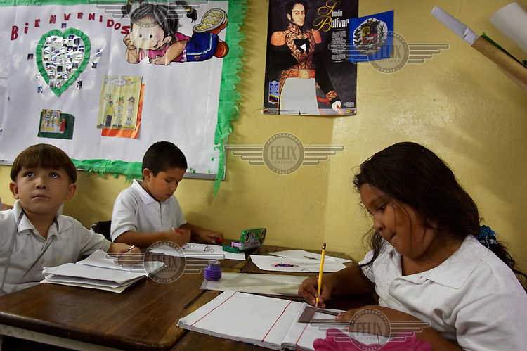 Students at a Bolivarian school in the poor barrio of 23 de Enero (23 January). Bolivarian schools have longer days than traditional schools, and provide breakfast and lunch for students. A portrait of Simon Bolivar hangs on the wall.