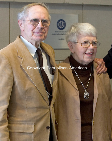 WATERBURY CT. 13 April 2015-041315SV08-David and Joan Reed of Middlebury stand by a plaque stating the David and Joan Reed Faculty Fellowship Endowment outside the community room at the school in Waterbury Monday. <br /> Steven Valenti Republican-American