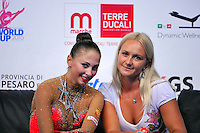 """(L-R) Daria Kondakova of Russia with coach smiles at """"kiss & cry"""" at 2010 Pesaro World Cup on August 27, 2010 at Pesaro, Italy.  Photo by Tom Theobald."""