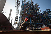 An Indian construction worker is seen at the site of the Adani Power plant of 4620 MW capacity in Mundra port industrial city of Gujarat, India. Indian power companies have handed out dozens of major contracts to Chinese firms since 2008. Adani Power Ltd have built elaborate Chinatowns to accommodate Chinese workers, complete with Chinese chefs, ping pong tables and Chinese television. Chinese companies now supply equipment for about 25% of the 80,000 megawatts in new capacity.