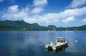 Boats in Lelu Harbor and view to Sleeping Lady mountain ridge profile; Kosrae, Micronesia.