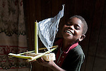 PEMBA, TANZANIA - DECEMBER - 7 : A boy plays with a boat made of banana plant leaves on December 7, 2010 on Pemba, Tanzania. (Photo by: Per-Anders Pettersson)