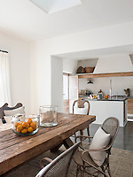 The open-plan kitchen dining area is furnished with a long rustic wooden dining table and has a contemporary and functional kitchen