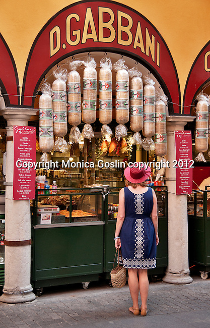 A woman wearing a blue dress and a red straw hat stands infront of the D. Gabbani store and deli, looking at the Italian Salami, in Lugano, Switzerland.