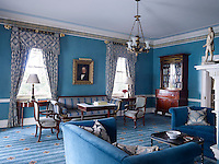 The blue living room, decorated with plush, soft furnishings and satins and antique walnut furniture