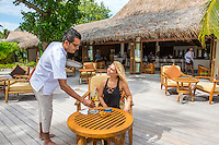 Maldives, Rangali Island. Conrad Hilton Resort. Woman having a drink at the resort (MR).