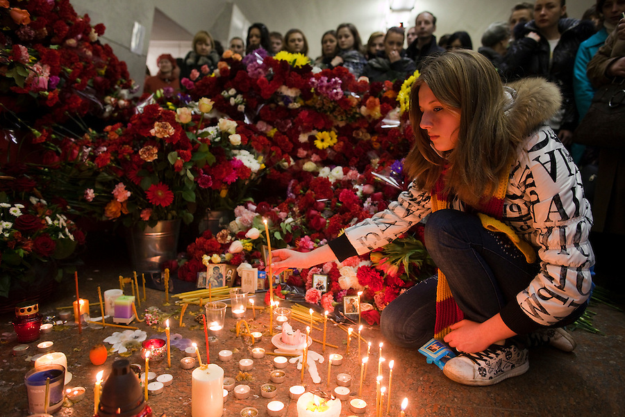Moscow, Russia, 30/03/2010..A young woman lights candles at a makeshift shrine on the spot inside Lubyanka metro station where a female suicide bomber blew herself up the previous day. At least 39 people were killed and 80 injured in the double blasts at Moscow metro stations during the morning rush hour.