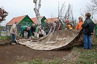Grundschulklasse, Schulklasse legt einen Schulteich, Schul-Teich, Teich, Gartenteich, Garten-Teich im Schulgarten an, zum Schutz der Teichfolie vor Steinen und Wurzeln wird ein Flies, Vlies in die Grube eingelegt