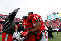 Ohio State Buckeyes running back Carlos Hyde (34) embraces a family member during Senior Day celebration before the college football game between the Ohio State Buckeyes and the Indiana Hoosiers at Ohio Stadium in Columbus, Saturday afternoon, November 23, 2013. The Ohio State Buckeyes defeated the Indiana Hoosiers 42 - 14. (The Columbus Dispatch / Eamon Queeney)