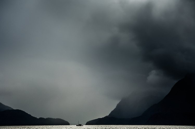 A lone fishing boat and stormy skies in Doubtful Sound, Fiordland, South Island, New Zealand - stock photo, canvas, fine art print