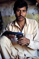 Pakistan   1986..A Pakistani tribal man with a built gun that is manufactured..Darra Adamkhel is Pakistan's largest weapons bazaar and factory, renowned for its gun making expertise since the late 19th century, Darra is a sprawl of hundreds of workshops where some 3,500 gunsmiths toil on replica weapons.