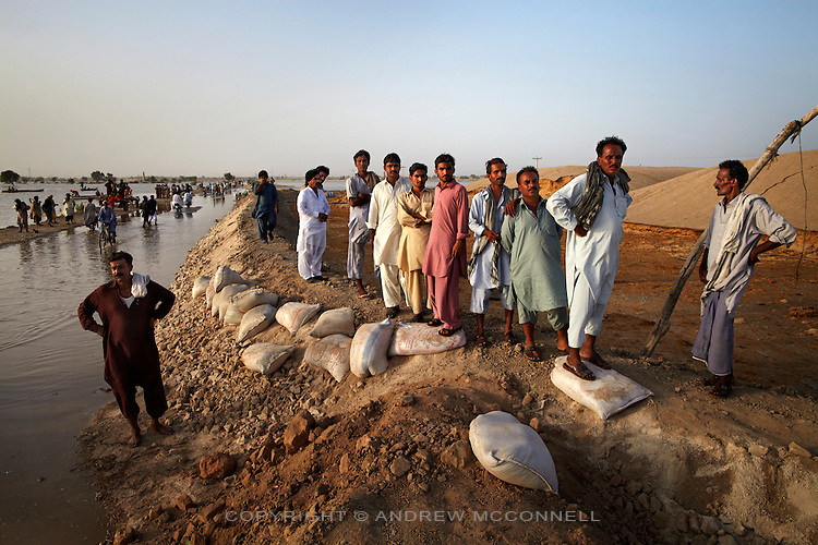 Men look on as flood water inundates the surrounding area after Manchar Lake bursts its banks. Officials made a breach in the lake's embankments to direct water away from the nearby cities of Dadu and Sehwan, in Sindh Province, Pakistan.