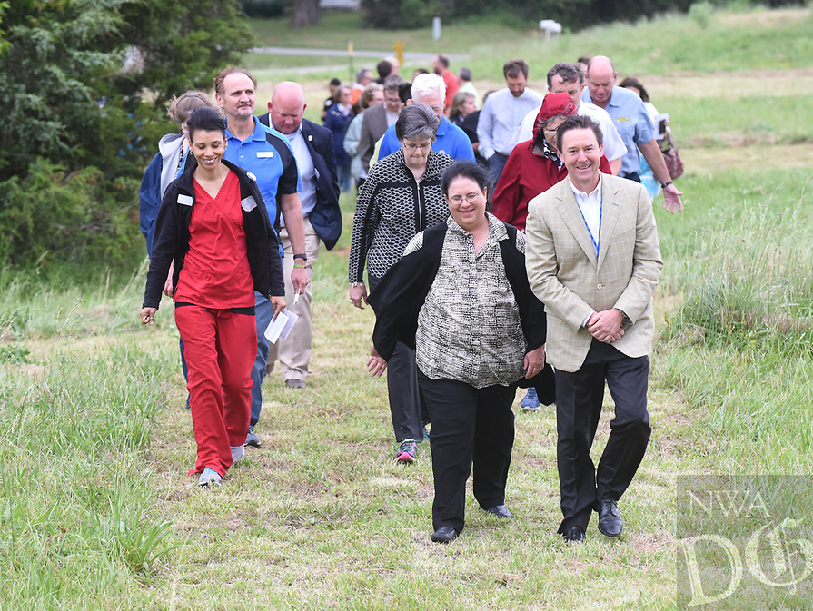 NWA Democrat-Gazette/FLIP PUTTHOFF <br />GARDEN BLESSING<br />Dr. Thaddeus Beck with Highlands Oncology Group in Rogers (forground right) takes part  Wednesday May 17 2017 in a blessing of the land walk at the site of the planned Healing Gardens of Northwest Arkansas. The garden will be built near the west entrance of Highlands Oncology Group on South 52nd Street. In addition to flowers, plants and trees, the garden will feature a waterfall, reflecting pool, sanctuary and walkways. The garden property is adjacent to the Razorback Greenway and will be open to the public. A campaign will begin soon to help fund construction, said Rev. Pamela Cicioni, spiritual director at Highlands Oncology Group. An estimated completion date has not been set. The blessing walk featured music and readings at various sites where garden features will be built.