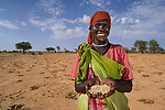 Pausing from planting, Adel Dut, a woman displaced by conflict in Sudan's Darfur region, displays sorghum seeds given to her by the United Methodist Committee on Relief. Since 2003, the conflict in Darfur has killed some 400,000 people and displaced about 2.5 million.