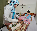 Asma Al-Taleb, a resident physician, examines Ibrahim Mustafa Al-Kikas in a hospital in Misrata, Libya. The nine-year old boy was injured on May 18 when a mortar fell near him during fighting between rebels and troops loyal to Libyan strongman Moammar Gadhafi. He was playing outside when he heard a hiss, then remembers nothing afterward. He has since had nine operations, including several skin grafts on his legs.