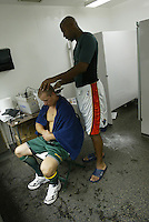OAKLAND, CA - SEPTEMBER 7:  Jermaine Dye cuts Mark Ellis' hair of the Oakland Athletics during the MLB game against the Boston Red Sox at Network Associates Coliseum on September 7, 2004 in Oakland, California. The Red Sox defeated the A's 7-1. (Photo by Michael Zagaris/MLB Photos via Getty Images)