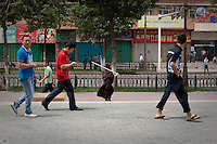 A Uighur woman carries a pole for protection in Urumqi. Ethnic violence between the Uighur and Han people had erupted in the city a few days earlier.