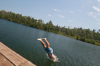 A young backpacker dives off a dock at McCargo Cove at Isle Royale National Park.