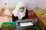 Asmaa Abu Hilal,18, a Palestinian blind studen writes on Braille machine at her family house in Rafah in the southern Gaza strip on Feb. 14, 2017. Abu Hilal superior at her study although there are no private schools for the blind in the city of Rafah. Photo by Ebtehal Shurab