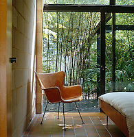 A 1950s fibreglass chair furnishes this tiled and breeze-block bedroom with a view over the steel gazebo and bamboo planting in the back garden