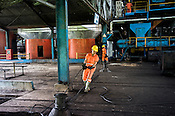 A factory worker pulls a heavy metal cable at the Sipef oil mill in Sumatra, Indonesia.