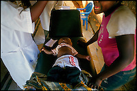 Kuito, Angola, May 22, 2006.Luciano Nene, 11 months, just died from anemia and cerebral malaria in the arms of his mother; children mortality is very high in Angola..Just 4 years after the end of a 25 year long civil war, Angola is starting to emerge again, yet a lot remains to be done: entire regions are still cut-off from the ouside world because of landmines and broken bridges, over 80% of the population lives below the poverty threshold in one of the potentially richest country in Africa. Natural ressources include oil, diamonds, gold and...water!.Malaria, tuberculosis, HIV/Aids are endemic, cholera and meningitis frequent.
