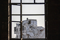 In this Sunday, Nov. 04, 2012 photo, a destroyed building is seen through a window in the nearby Qastal Al-Harami battlefield after several weeks of intense battles between rebel fighters and the Syrian army in the Jdeide district of Aleppo, the Syrian's largest city. (AP Photo/Narciso Contreras).