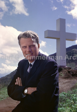 Reverend Billy Graham beneath giant cross at Kolekole Pass, Hawaii, 1963. The giant steel cross was erected by the Army in 1962 and dismantled in 1997 after a federal lawsuit alleging failed separation of Church and State. Photo by John G. Zimmerman.