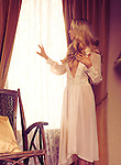Beautiful young woman with long blond hair wearing a white night gown standing by the window and looking out