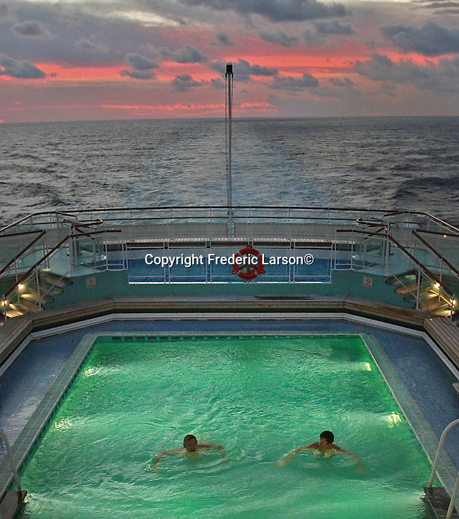 A couple enjoys a morning dip in one of the several pools at the sten of the Queen Mary 2 as it steams north towards San Francisco, California.