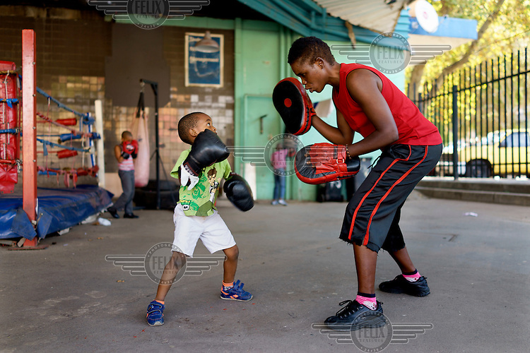 Natalie Baniea trains a young boy during an afternoon session at the George Khosi's Hillbrow Boxing Club. As the club does not have the resources to provide child-size equipment, the youngsters make do with adult gloves.  Hillbrow, in downtown Johannesburg, is the city's most notorious neighbourhood. It is overcrowded, ridden with illegal squats and suffers from high levels of crime much of which is related the thriving illicit drug trade. Against this backdrop, George Khosi's story is not atypical. A childhood spent on the streets, where he survived by committing petty crime and hustling, led to imprisonment at the age of 16. Because he was big and looked older than his age this incarceration was in an adult institution. Here he began to fight since, as he says 'they wanted to make me a woman and I didn't want to be a woman.' When he got out, he took up boxing in earnest.His prospects as a professional boxer looked bright until he was shot and left for dead during a burglary. He lost his right eye and now walks with a limp. His boxing career seemed over but George picked up his gloves again, this time to teach Hillbrow's youngsters. His gym became a place of hope and discipline for local youth, keeping them of the streets and even producing some national champions.
