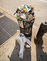 An overflowing trash can in the Chelsea neighborhood of New York on Saturday, July 11, 2015. (© Richard B. Levine)