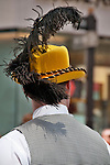 A man in the New York City Easter Parade wearing a bright yellow hat with a large black feather on it