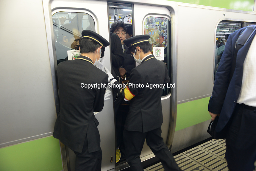 Railway staff squeeze passengers onto full trains and force the doors closed during morning rush hour, Shinjuku Station, Tokyo. With up to 4 million passengers passing through it every day, Shinjuku station, Tokyo, Japan, is the busiest train station in the world. The station was used by an average of 3.64 million people per day.  That&rsquo;s 1.3 billion a year.  Or a fifth of humanity. Shinjuku has 36 platforms, and connects 12 different subway and railway lines.  Morning rush hour is pandemonium with all trains 200% full. <br /> <br /> Photo by Richard jones / sinopix