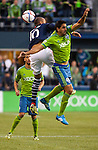 Seattle Sounders Leo Gonzales (12) and New England Revolution Teal Bunbury (10) go for the ball during an MLS match on March 8, 2015 in Seattle, Washington.  The Sounders beat the Revolution 3-0.  Jim Bryant Photo. ©2015. All Rights Reserved.