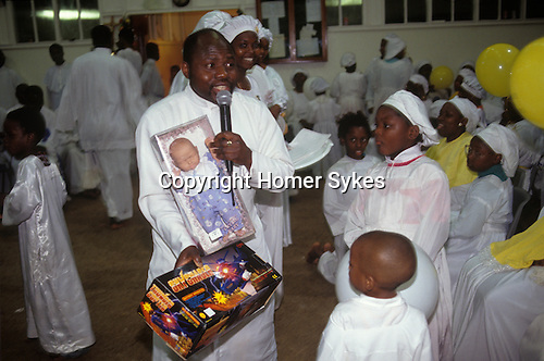 The Celestial Church of Christ London. Pastors shows children members of the congregation toys which have been brought for them.  from A STORM IS PASSING OVER a Look at Black Churches in Britain. Published by Thames and Hudson isbn 0 500 27826 1