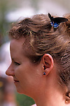 Woman at the  Woodland Park Zoo butterfly exhibit with a butterfly in her hair Seattle Washington State USA.