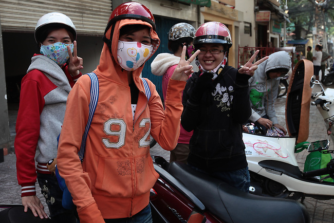 A group of young women gear up to ride their motorbikes in Ho Chi Minh City, Vietnam. Women in the country are fanatical about exposing as little of their skin to the sun as possible, and hooded jackets, masks and gloves are considered essential commuting gear in the city. July 3, 2011.