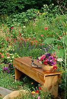 wooden bench in garden with vase of fresh cut flowers