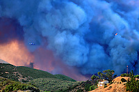 870000033c fire fighting plane and heilicopter emerge from a giant smoke cloud over an uncontrolled wildfire in the simi hills above chatsworth in los angeles county california