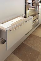 A built-in fridge and fully integrated freezer drawer is finished in glossy natural aluminium