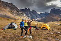 Three hikers wearing crocks enjoy the scenery of the Arrigetch Peaks surrounding their tents at camp on the tundra in Alaska's Gates of the Arctic National Park, Alaska.
