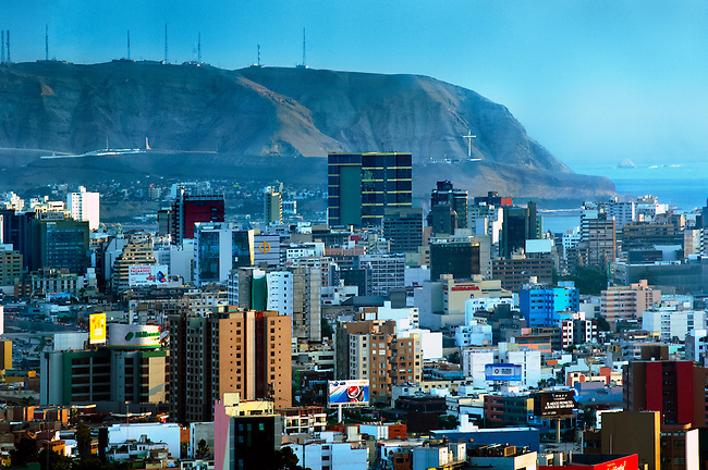 The Miraflores district of Lima, Peru is an upscale neighborhood of hotels and condominums.   Many tourist are attracted to its shopping areas and beaches.  The steep cliffs of the promontory Morro Solar with its illuminated cross is seen in the background.