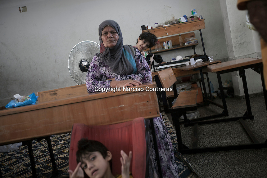 "In this Saturday, Aug. 16, 2014 photo, Mahmod (front), a 14 yo teenager who is mental disable, Malak (back), a 13 yo who is mental disable, and their grandmother (middle), are seen inside a classroom at the Al-Zaytoon UN School turned into a temporary refugee after their family fled from Shuyaja neighborhood when the IDF targeted and destroyed their house during the ""Protective Edge"" military operation in Gaza Strip. Mahmod and Malak are two of four mental disable brothers and sisters of the father Jawal's family (not pictured).  (Photo/Narciso Contreras)"