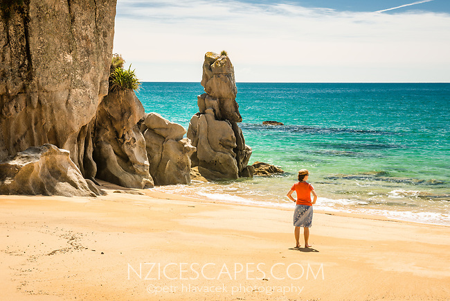 Young woman on pristine Anapai Bay with its granite rock formations on Abel Tasman Coast Track, Abel Tasman National Park, Nelson Region, South Island, New Zealand