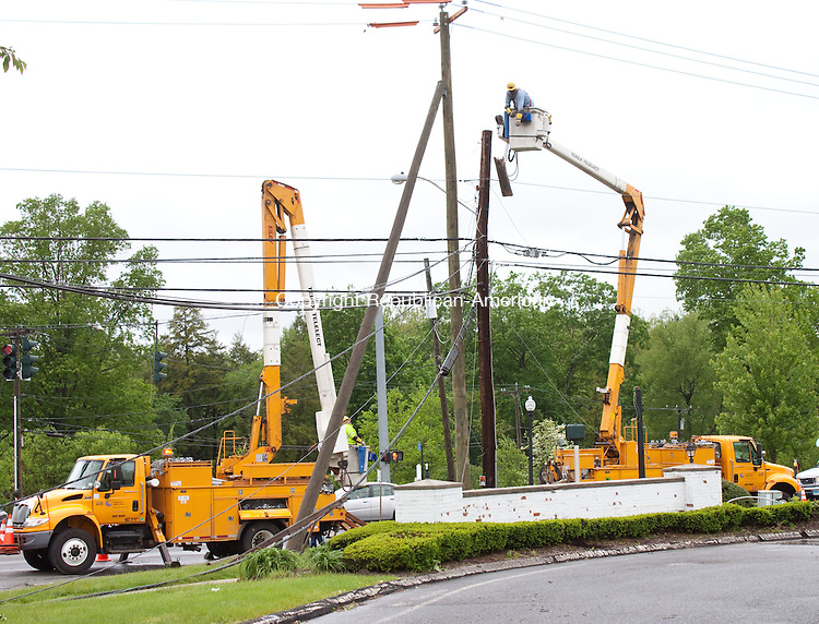 SOUTHBURY CT- MAY 14 2014 052814DA03-  A CL&amp;P employee begins to disassemble a utility pole on the corner of Peter Rd. and Main St. South in Southbury that was destroyed during Tuesday nights storm. <br /> Darlene Douty Republican American